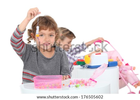 Little girls playing with toys - stock photo