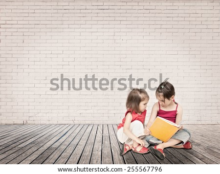 little girls reading a book sitting on a wood floor - stock photo