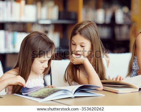 Little girls reading books in library - stock photo