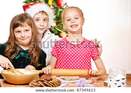 Little girls rolling dough to make Christmas cookies - stock photo