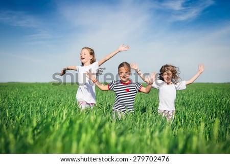 Little girls running on the field - stock photo