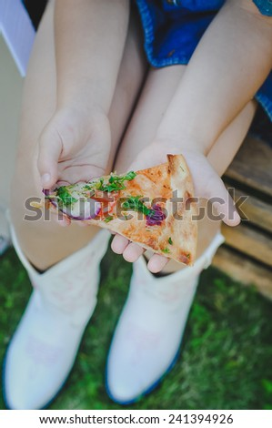 Little girls's hands holding a portion of pizza - stock photo