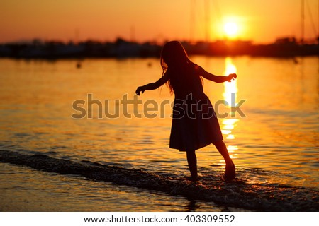 Little girls silhouette by sea bay on sunset with boats and yachts in a background - stock photo