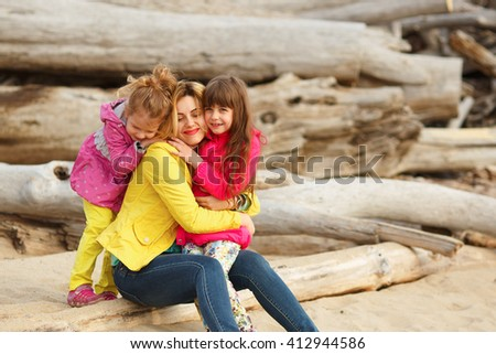 little girls sisters hug their mom - stock photo