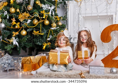 Little girls, sisters, sitting with gifts near a Christmas tree. Family New Year celebration. 2017 - stock photo
