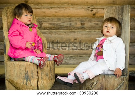 little girls sitting on the wooden chairs - stock photo