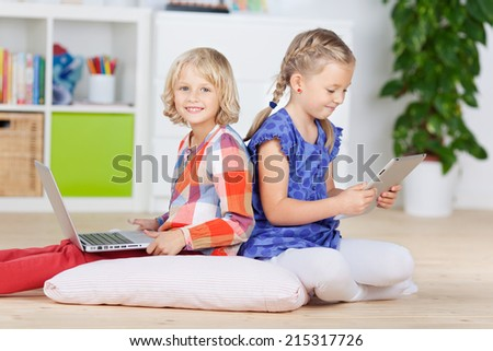 Little girls using laptop and Tablet-PC at home - stock photo