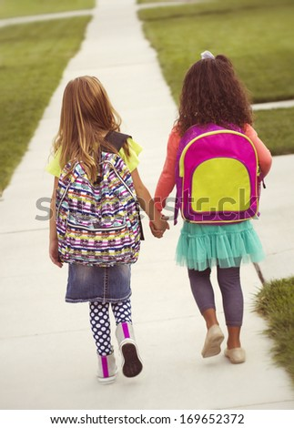 Little girls walking to school together, vintage tone - stock photo