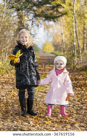 little girls wearing rubber boots in autumnal nature - stock photo