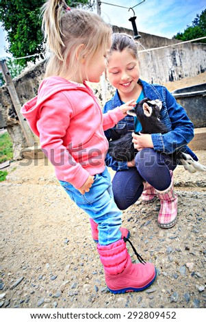 little girls with a goat kid in front of the farm