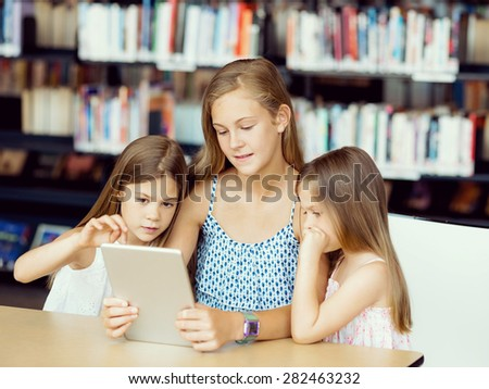 Little girls with a laptop in library - stock photo