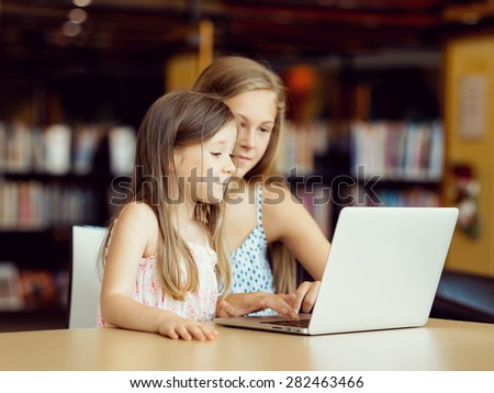 Little girls with a laptop in library