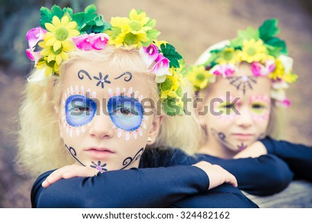 Little girls with black clothing and sugar skull makeup - stock photo