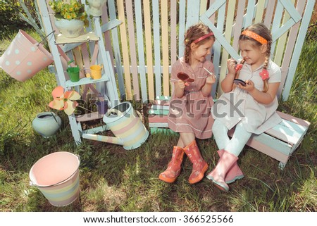 Little girls with lipstick and holding mirror in garden - stock photo