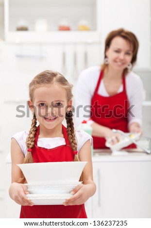 Little girtl helping mother to do the dishes carrying the plates