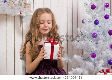 Little gLittle girl with christmas present in front of fir tree, focus on girl - stock photo
