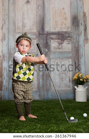 Little golfer.  Adorable toddler dressed as a little golfer. - stock photo