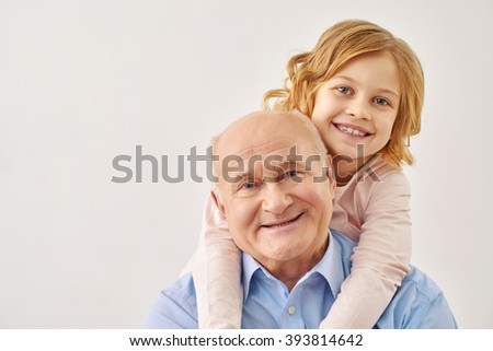 Little granddaughter hugging her grandfather - stock photo