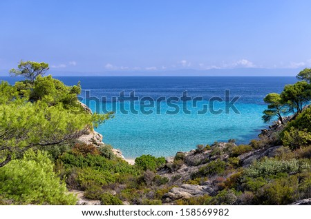 Little gulf hiding a small sandy beach in Sithonia, Chalkidiki, Greece, with the forest reaching to the sea