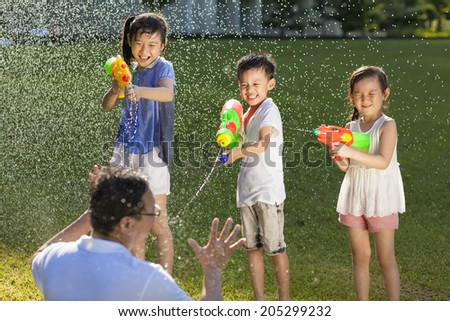 little guys using water guns to spray their father - stock photo