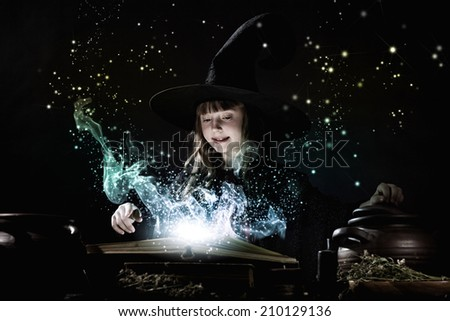Little Halloween witch making magic with stick - stock photo