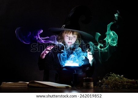 Little Halloween witch reading conjure above pot - stock photo
