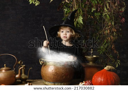 little halloween witch with cauldron, outdoors - stock photo
