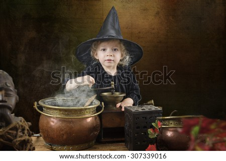 little halloween witch with smoking cauldron - stock photo