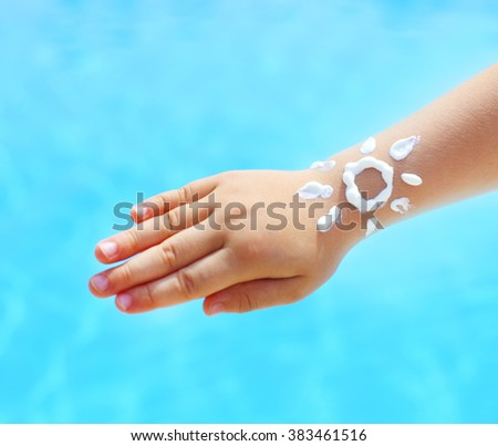 Little hand of the baby with suntan lotion near the pool in form of the sun - stock photo