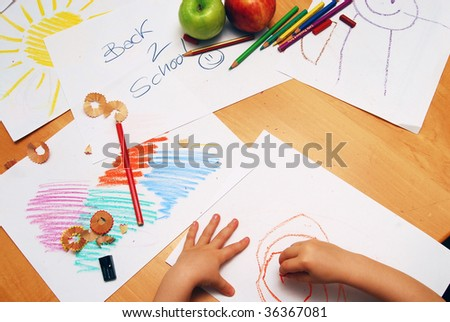 Little hands drawing between school supplies and apples - stock photo