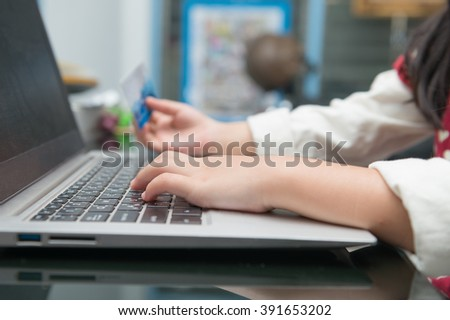 little Hands holding credit card and using laptop. Online shopping