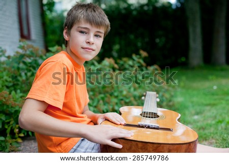 Little handsome boy sitting on the porch with guitar - stock photo