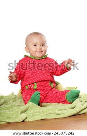 little happy baby girl sitting on a green towel