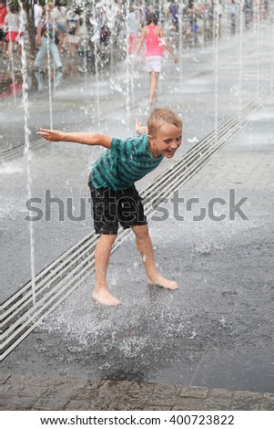 Little happy boy has  fun in outdoor fountain at hot day - stock photo