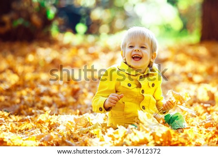 Little happy boy in yellow jacket is playing with leaves at golden autumn park background. - stock photo