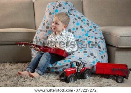 Little happy boy plays the guitar hits, sitting at home on the floor - stock photo