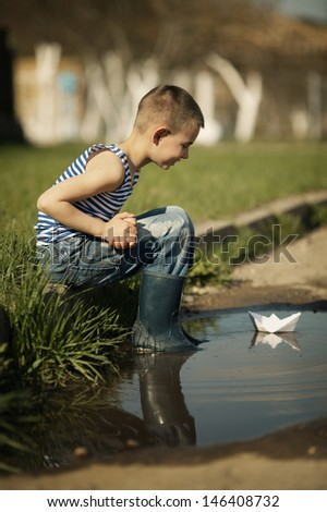 little happy boy plays with paper boats in puddle - stock photo