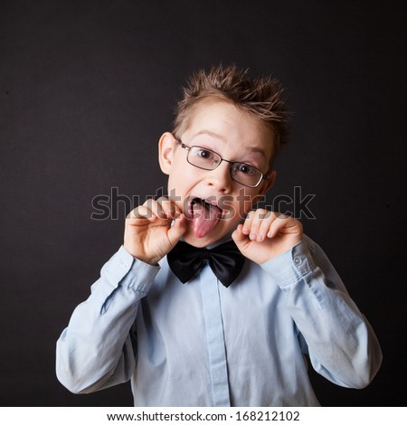 Little happy boy showing his tongue against the black - stock photo