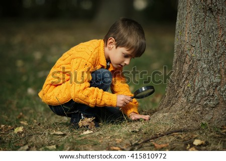 little happy boy with magnifying glass - stock photo