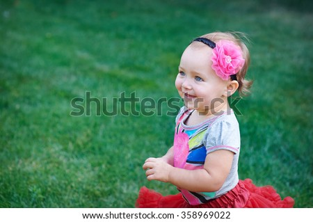 little happy cheerful girl running around playing and having fun in the summer on the nature - stock photo