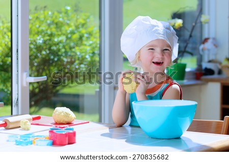 Little happy child, adorable toddler girl in white chef hat helping mother cooking delicious pasty in the kitchen