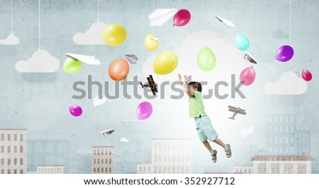 Little happy cute boy flying on balloon