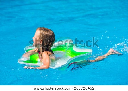 Little happy cute girl in outdoor swimming pool