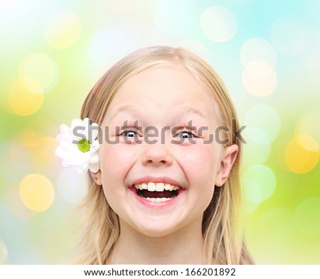 Little happy girl against blurred background. - stock photo