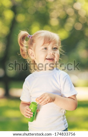 Little happy girl blowing soap bubbles in the parc - stock photo