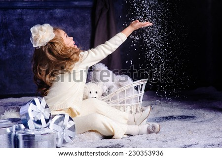 little happy girl celebrating christmas with gift box and playing snow - stock photo