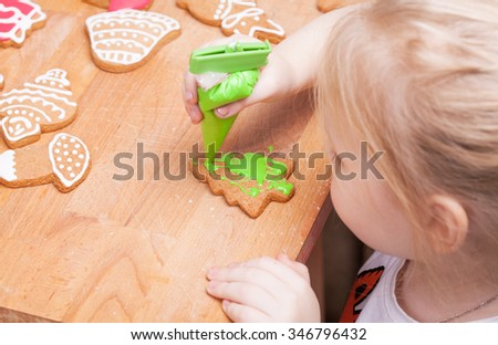 Little happy girl decorates Christmas gingerbread cookies using red glaze, selective focus