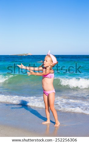 Little happy girl during tropical beach vacation - stock photo