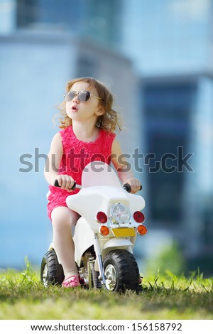 Little happy girl in sunglasses rides on toy motorbike on grass near skyscrapers. - stock photo