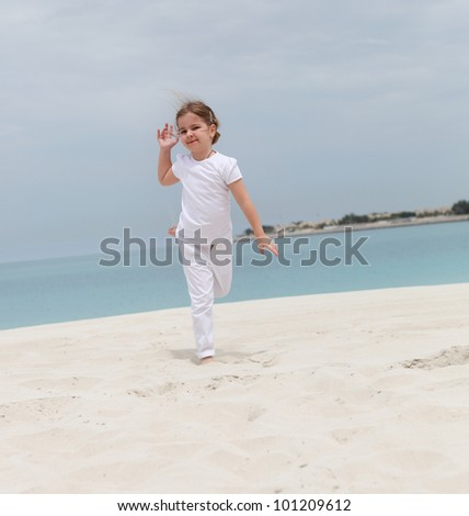 Little happy girl in white running on the beach